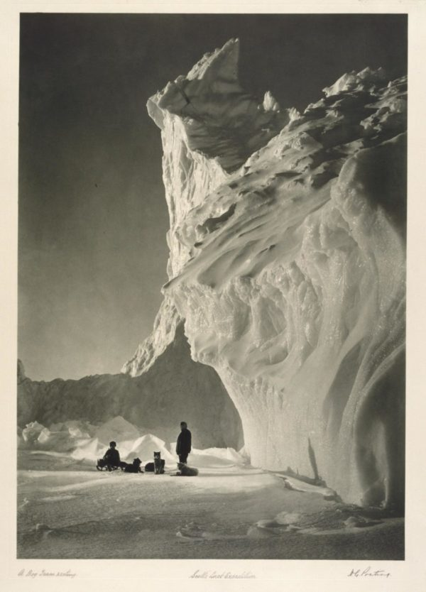 A black and white image of a cavern in an iceberg and some members of the expedition.